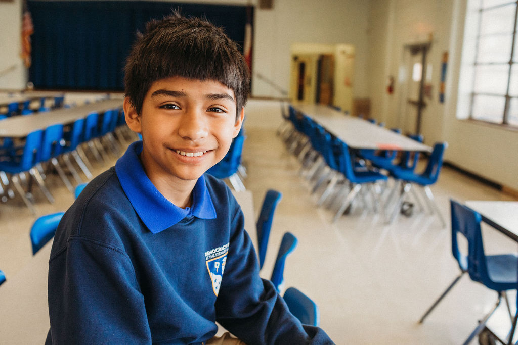 Boy smiling at the camera in a cafeteria
